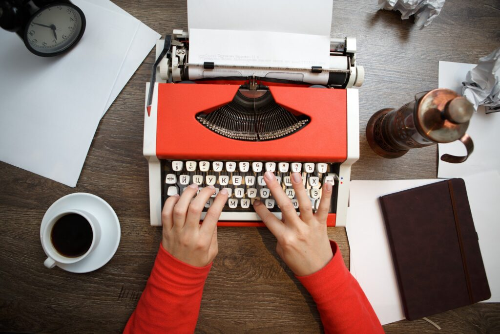 Vintage red typewriter with blank paper on wooden desk